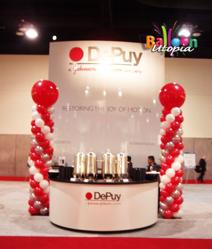 Large balloon columns help this trade show booth attract attention